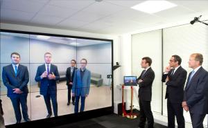 Emmanuel Macron et John Chambers lors de l'inauguration du centre devant un mur vidéo interactif.
